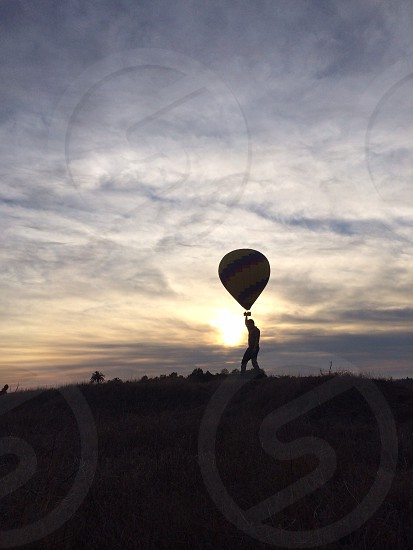 man on top of the hill holding a hot air balloon photo