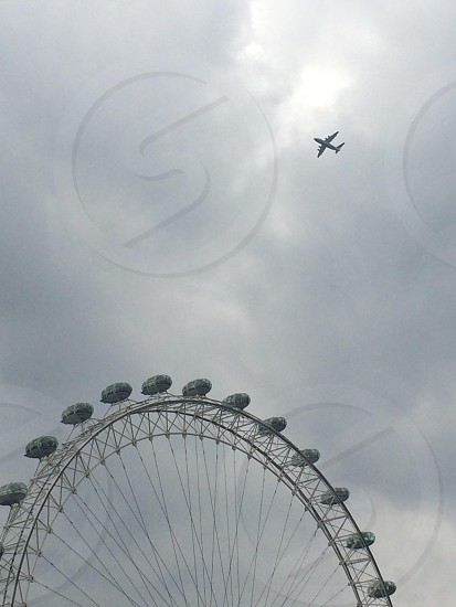 An aircraft flying over The London Eye. London. UK. photo