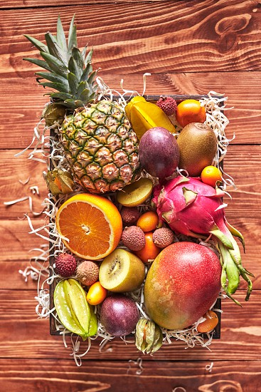Summer exotic fruits in a box with fresh juicy ingredients - carambola pineapple dragon fruit mang litchi phisalis orange kiwi kumquat passion fruis on a wooden background. Top view. photo