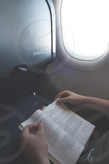 A man reading a book on a plane photo