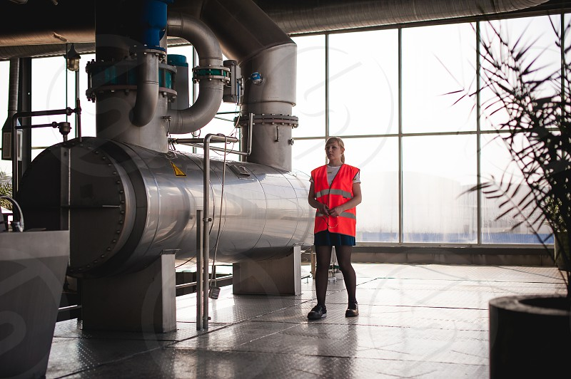 Female worker on beer factory. portrait woman in robe standing on background line Food production Inspection management control Equipment for production and bottling finish product end-user buyer photo