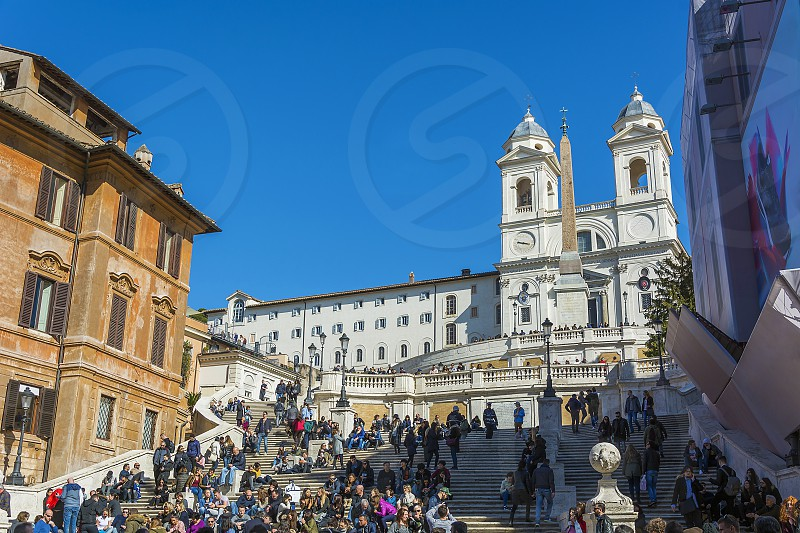 Crowd at Spanish Steps in Rome. The Spanish Steps (Scalinata di Trinità dei Monti) are a set of steps climbing a steep slope between the Piazza di Spagna at the base and Piazza Trinità dei Monti dominated by the Trinità dei Monti church at the top. photo