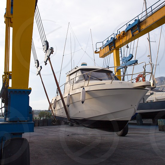Boat wheel crane elevating motorboat to yearly paint task photo