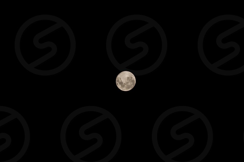 The big full moon over a dark sky background photo