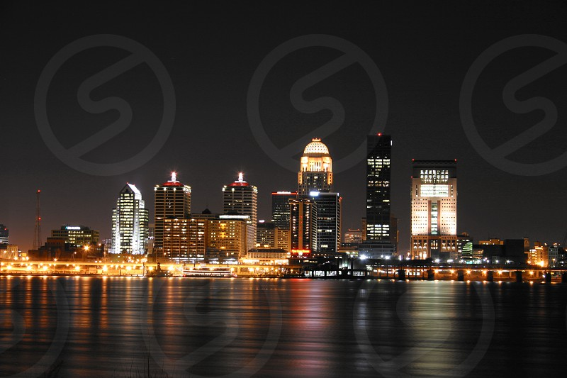 Night time photo of the Louisville Kentucky Skyline with Ohio river in the foreground. photo