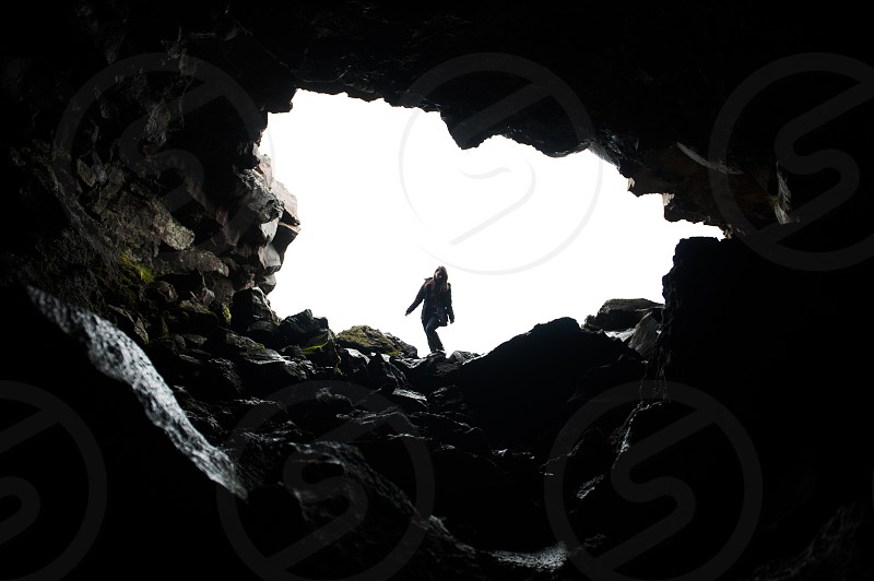 silhouette of woman hiking along mouth of cave photo