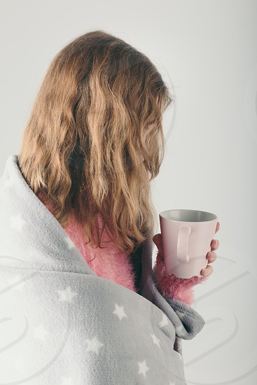 Young woman has caught cold has day off sick day wrapped in blanket holds cup of herbal tea. Profile portrait view photo
