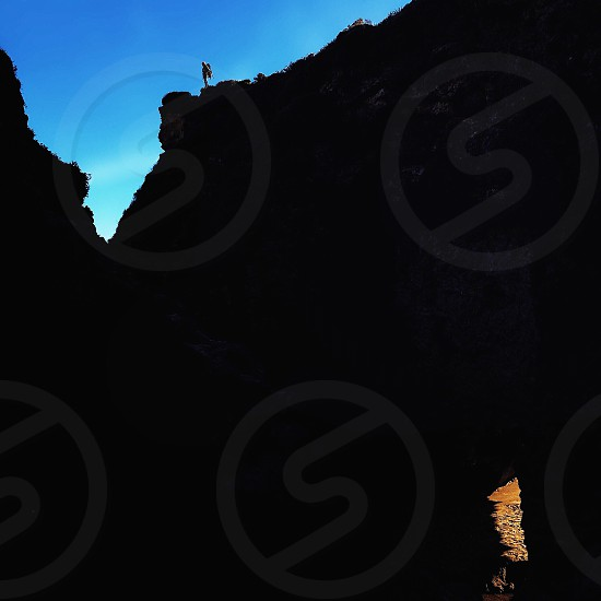 person standing atop cliff photo