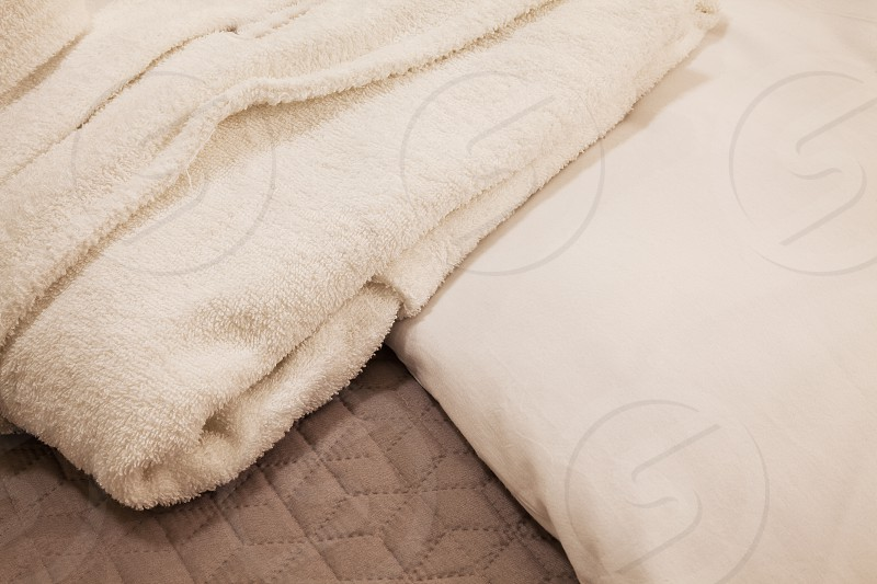 Hotel room details closeup view on white and clean bathrobe on bed.  photo