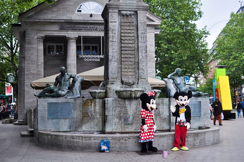 Mickey and Minnie Mouse mascots standing beside gray concrete water fountain photo
