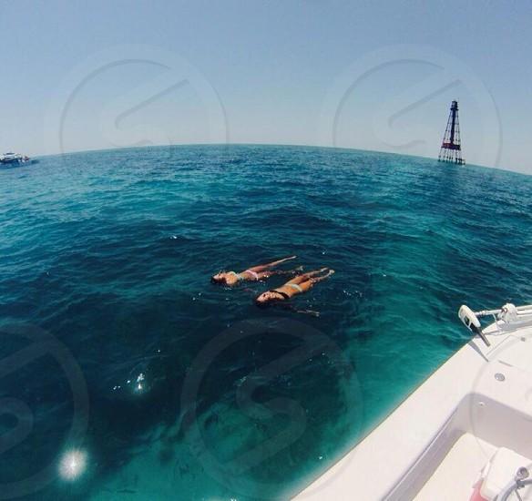 2 women swimming near white boat photo