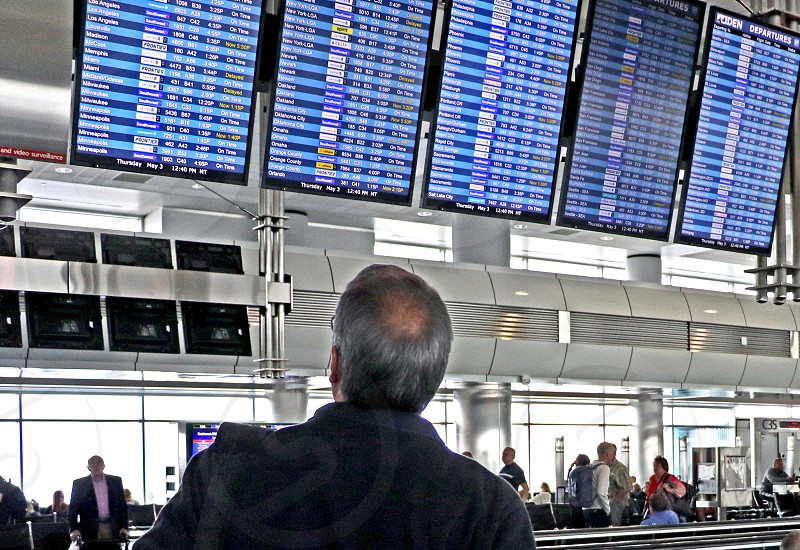 A traveler checks the flight information board at the airport for his departure time and gate photo