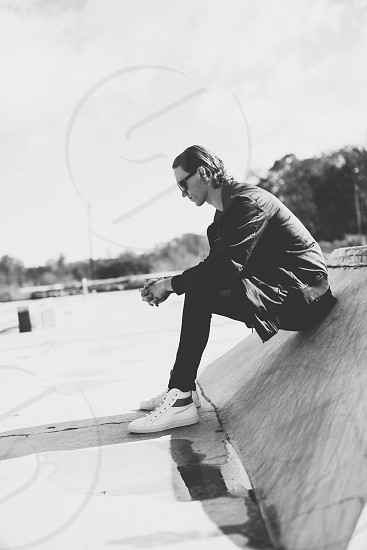 grayscale photo of man in black long sleeve shirt black skinny pants and white black high top sneaker sitting on grey concrete incline wall photo