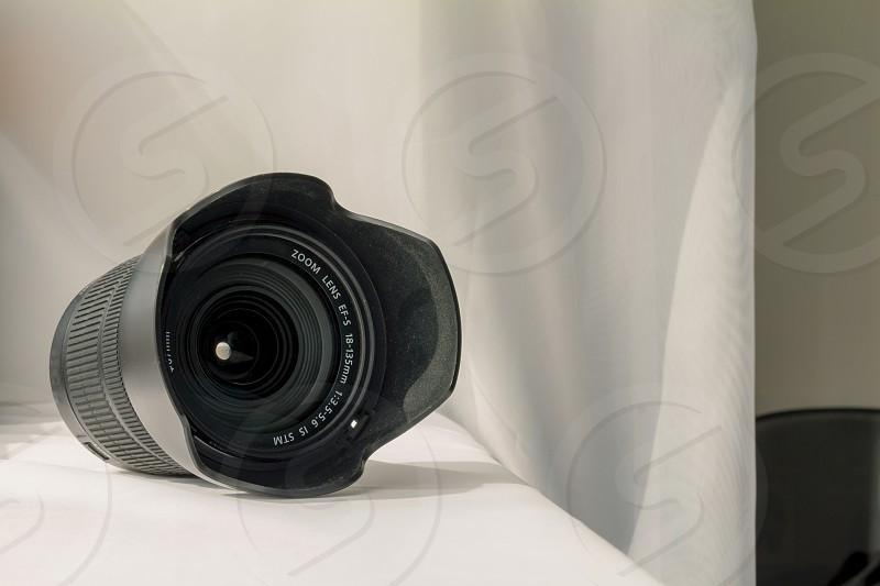 Black camera zoom lens on white cloth. photo