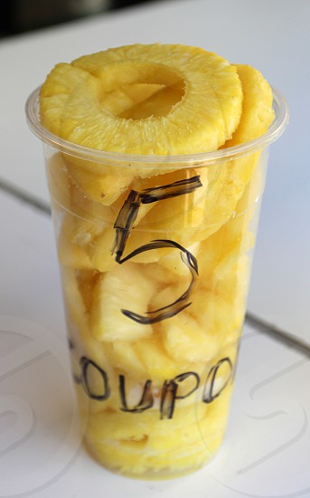 Fresh pineapple slices in a cup  state fair food photo