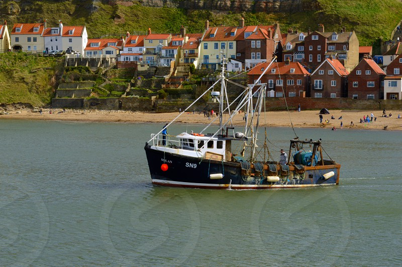 Fishing boat heading out to sea against the beach and part of the seaside village of Whitby UK in the background. photo