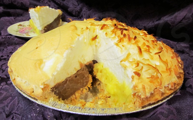 Half and half coconut and chocolate meringue pie whole pie with slice out on purple background photo