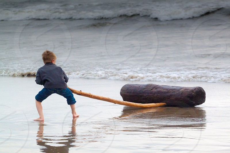 A Boy Moving a Log on a Beach into the Ocean. Persistence photo