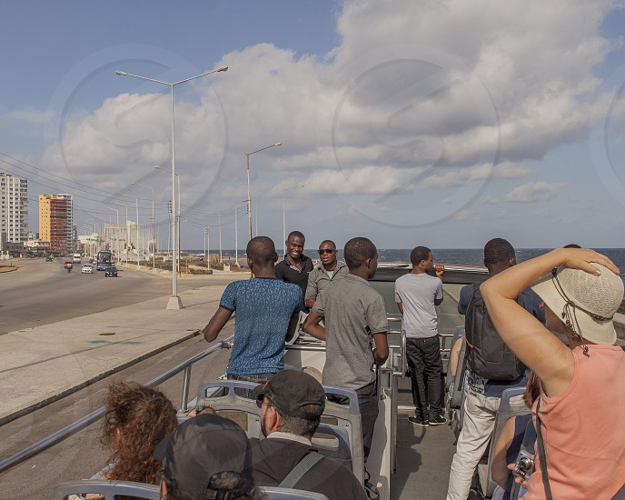 Cuba tourism Havana Malecón people bus sky beach city road sea cloud photo