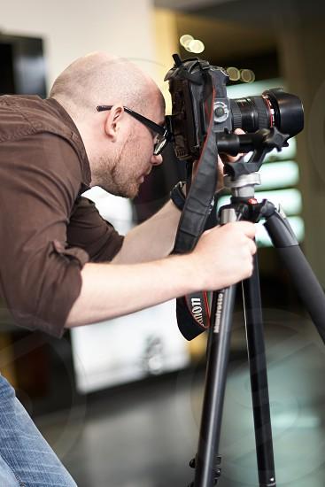 camera man in black eyeglasses performing dslr camera on tripod photo