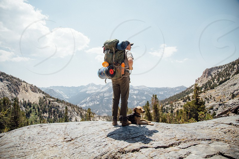 man standing on top ogfthe mountain with his dog photo