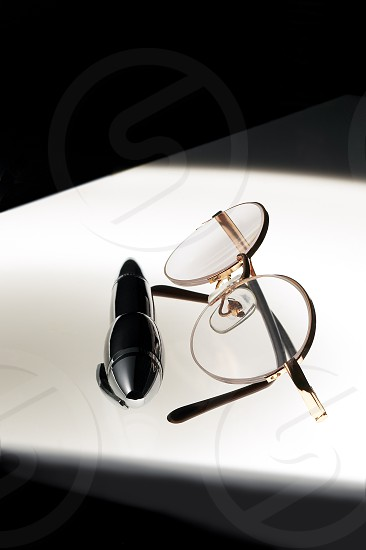 pen and glasses over white glass table photo