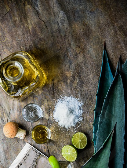 Variety of tequilas blue agave leaves shot on slate surface photo