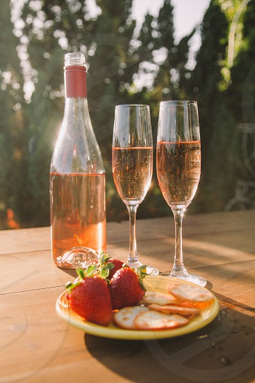 two champagne flutes filled with rose wine next to the wine bottle and a plate of strawberries and crackers photo