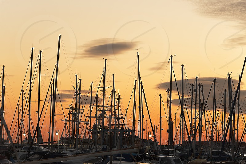 Masts of boats during a sunset in the port of Alicante Spain. photo