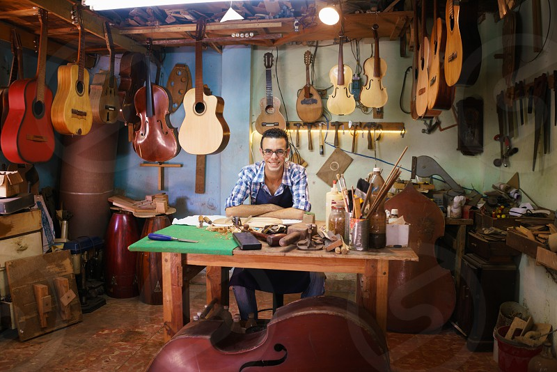 portrait; lute; luter; lutemaker; maker; artisan; smile; man; happy; cheerful; guitar; looking at camera; crafts; acoustic; classical guitar; adult; assembling; caucasian; confidence; confident; craftsman; creative; dedication; expertise; handmade; inspired; luter shop; making; mandolin; music; one person; owner; people; profession; professional; proud; shop; skilled; small business; string instrument; studio; violin; wood; wooden; work; working photo