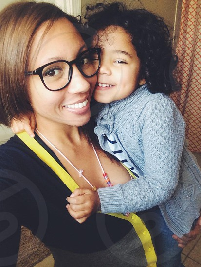 woman wearing black long sleeved shirt standing beside baby girl photo