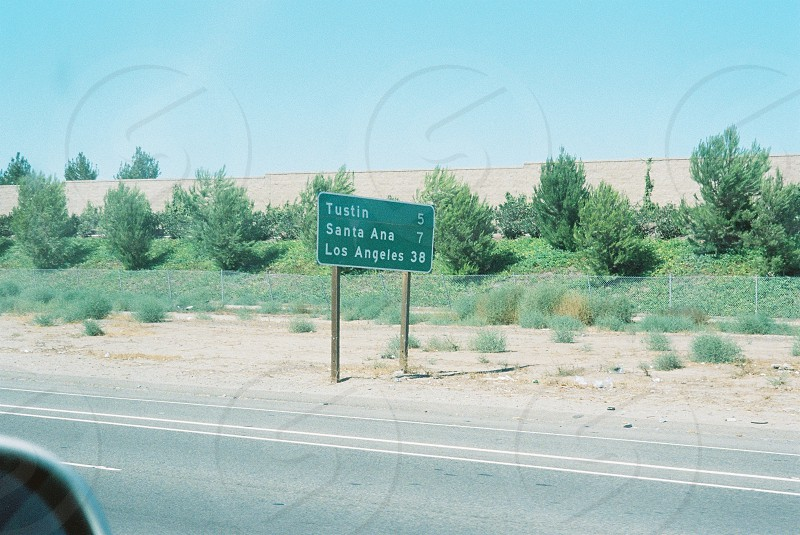 tustin santa ana and los angeles green and white road sign near gray and yellow road under blue sky photo