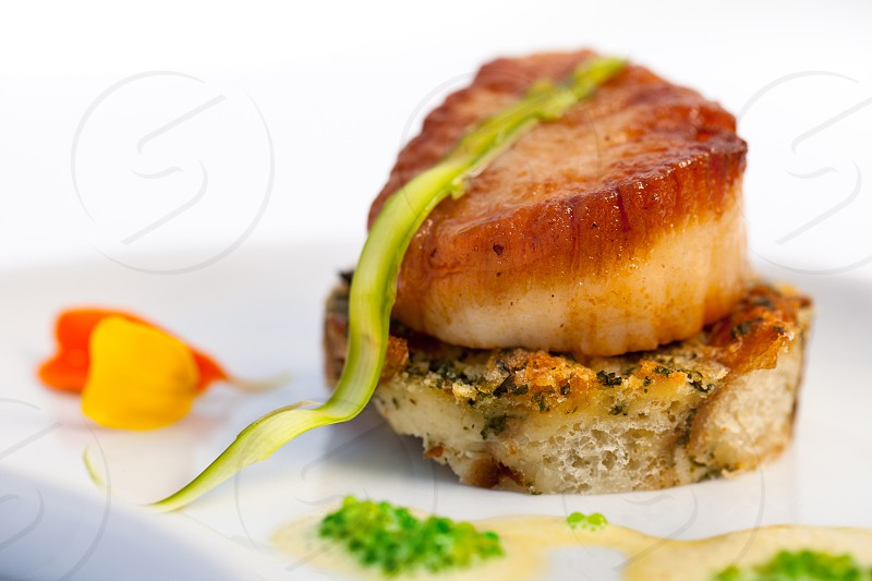 A high key photo of perfectly seared scallop on a gourmet slice of seasoned toast with a decadent fish roe sauce. photo