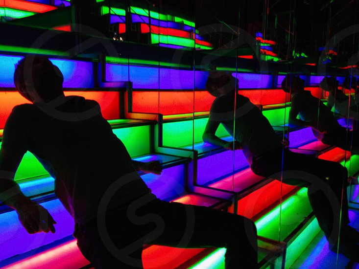 man lying on rainbow lighted staircase photo