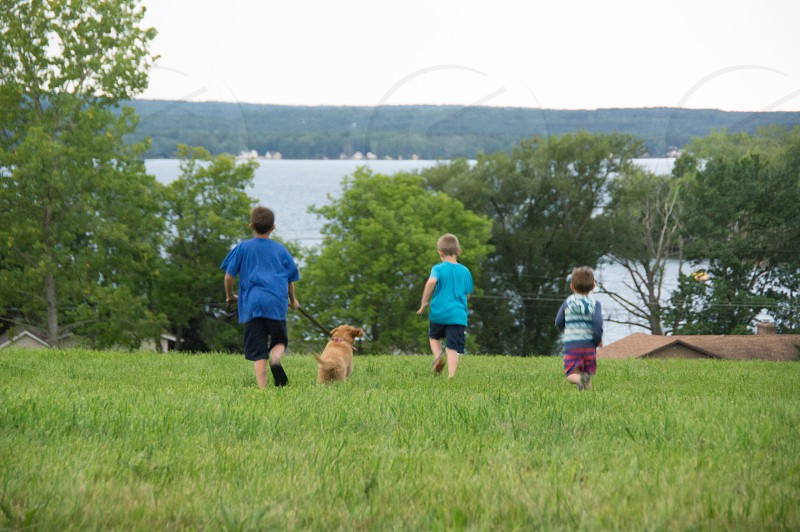 Kids running boys dog field grass hillside photo