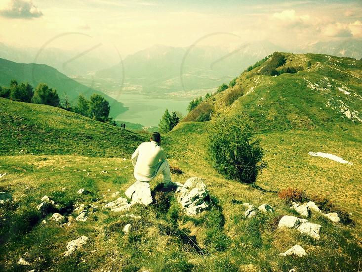 man sitting facing green mountain photo