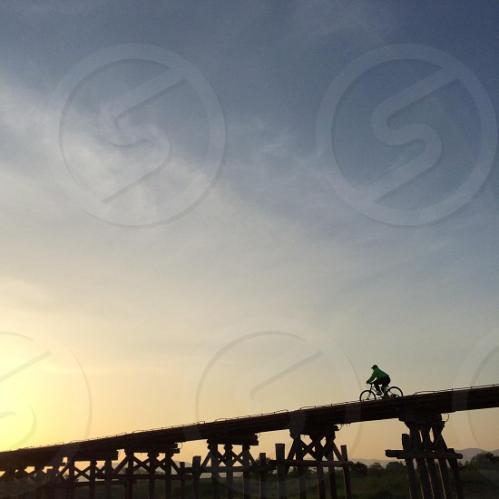 person driving bicycle on a bridge photo