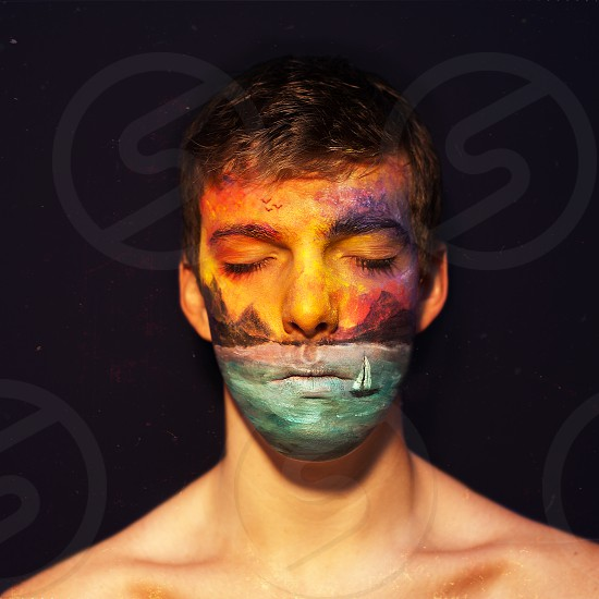 man with multicolored painting on his face photo