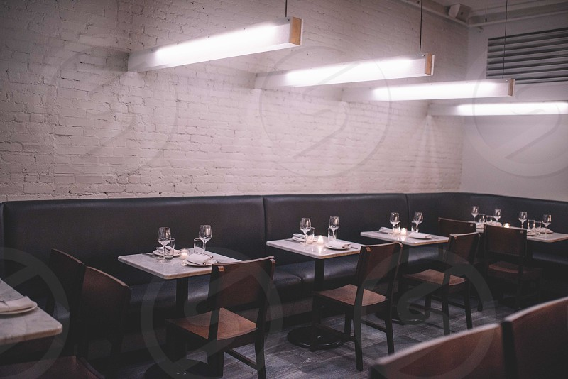restaurant interior with set'ed utensils on the brown and white rectangular table with black leather sofa on the corner and singular back chair with open lights photo