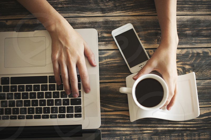 Female working on laptop and drinking delicious coffee with mobile phone on the table photo