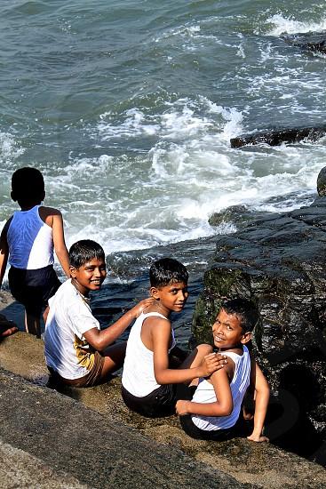 indian school children in Mumbai playing in the ocean photo