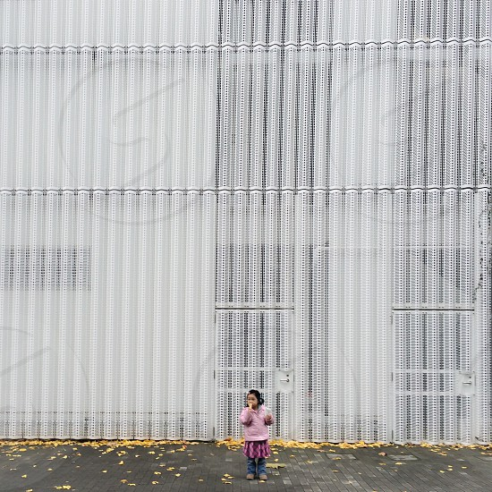 girl in pink jacket on grey sidewalk by white wall photo