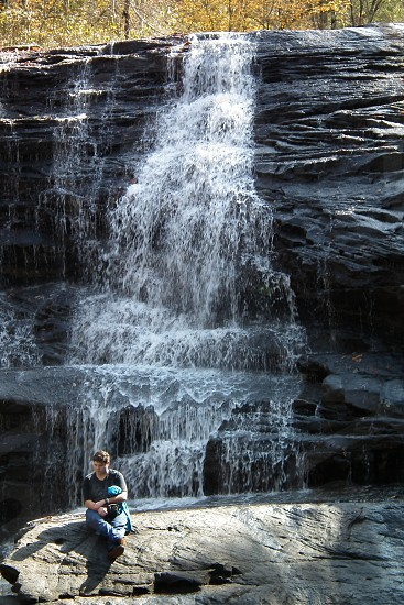 man thinking in front of waterfall photo