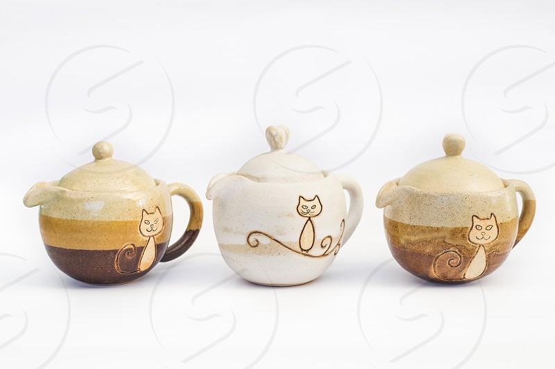 three ceramic teapots stoneware with white background photo