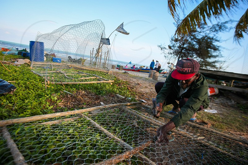 A fisherman diligently making fish trap to trap crabs and fish at the Pantai Batu Hitam (Black Stone Beach) Kuantan Malaysia. photo