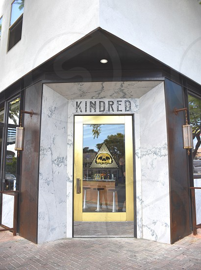 kindred brown white door signage during daytime photo