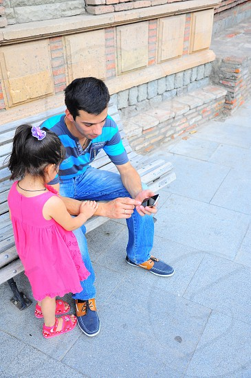 girl standing with a man seated on a park bench photo