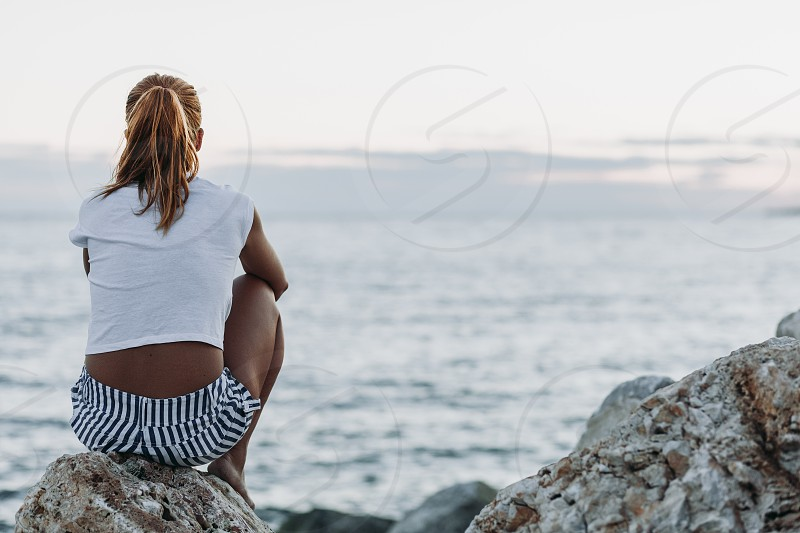 Young woman feeling sad by the sea photo