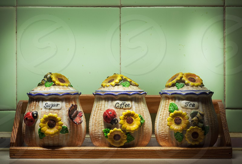 Closeup view of three old and dirty decorative bowls for tea coffee and sugar in front of tiled green wall. photo
