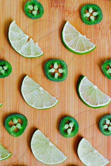 Five Senses - Flat lay of lime and jalapeño slices arranged on a bamboo cutting board photo